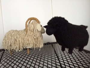 Soft sculptures - white ram facing black sheep