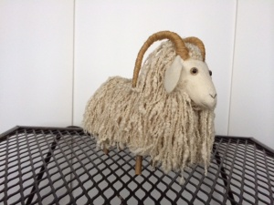 soft sculpture of goat with white locks and horns