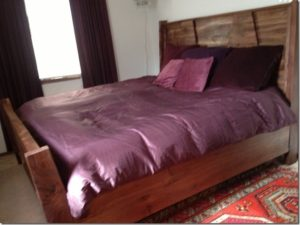 wooden bed with violet duvet
